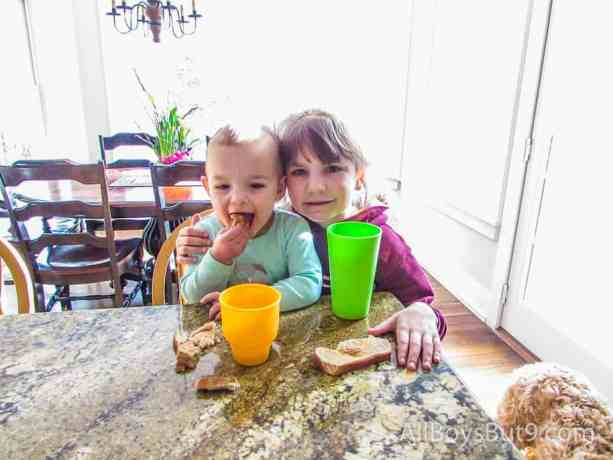 2 little girls, age 2 and 7, sitting at breakfast together.