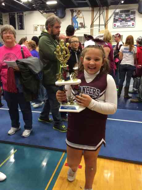 Zoie Grace holding the cheer-team trophy.