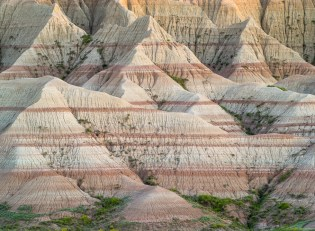 Soft warm light at dusk gives shape to patterns and lines in the Badlands