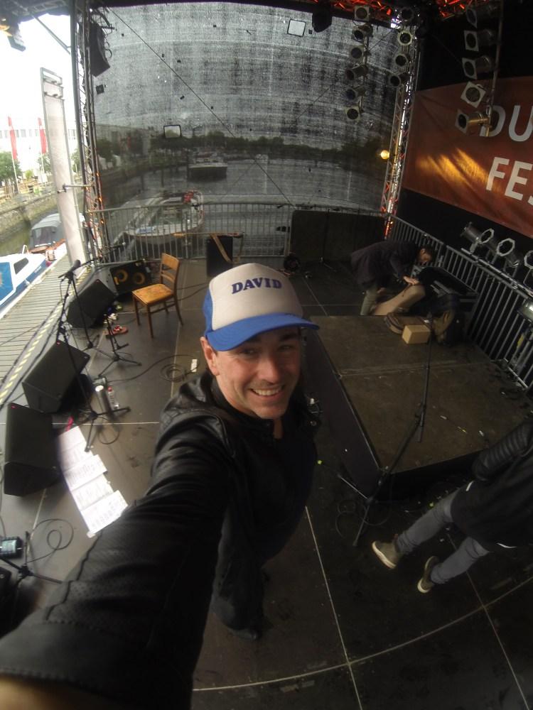 David Alleckna, der hamburger Bassist, macht einen Selfie auf der Bühne des Duckstein-Festivals in Lübeck vor seinem Auftritt mit dem Sänger Sebó. Im Hintergrund sieht man Verstärker, Mikrofone und Instrumente.