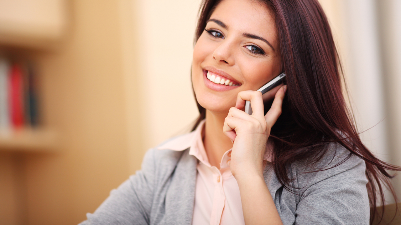 Image of brunette woman talking on her cell phone and smiling