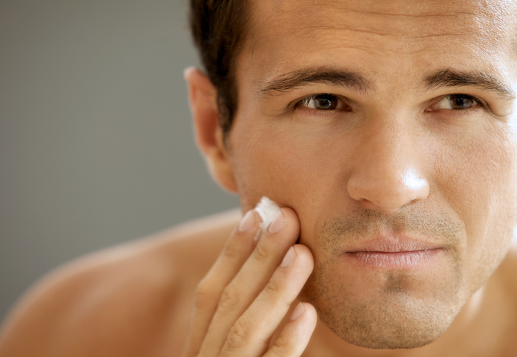 Image of a handsome man applying moisturizer on his skin