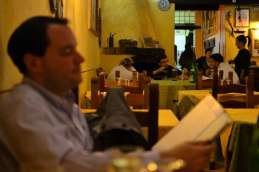 Robert peruses the menu while the wait staff relax ~ customer service in Rome is far different from home