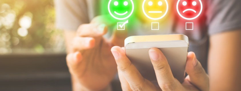 image of man typing on cell phone with smily face for marketing excellence review article