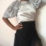 La camiseta Bloom de cuerpo en seda con mangas abullonadas tejido a mano en crochet es el reflejo de la belleza y exuberancia del ganchillo.
