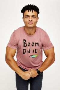 Male model in pink flexing arms