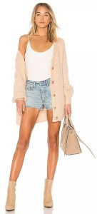 A woman wearing a tan buttoned Tularosa cardigan sweater off of one shoulder.