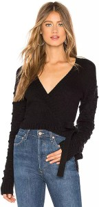 A woman wearing a black knit wrap sweater with high waisted jeans.