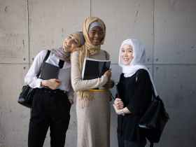 positive multiracial muslim women with workbooks in university
