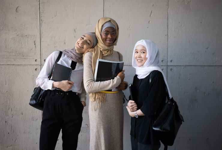 positive multiracial muslim women with workbooks in university