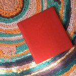 A red photo album on my colorful concentric circle rag rug in my apartment in Boston.