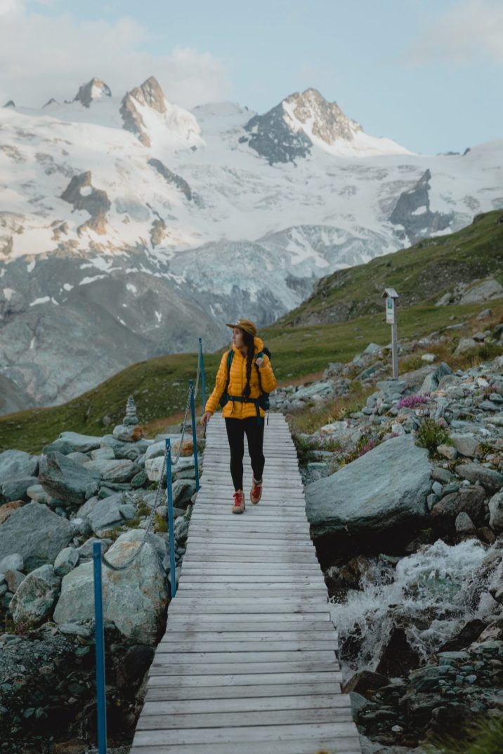 Girl hiking on a bridge with a mountain in the background