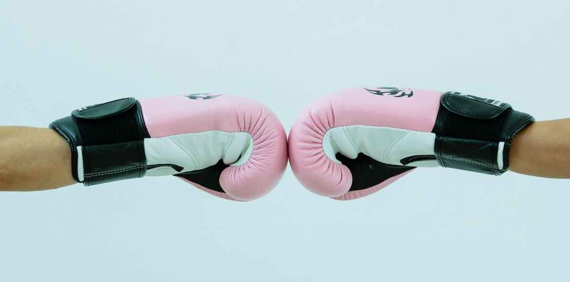 faceless people in boxing gloves giving fist bump in studio
