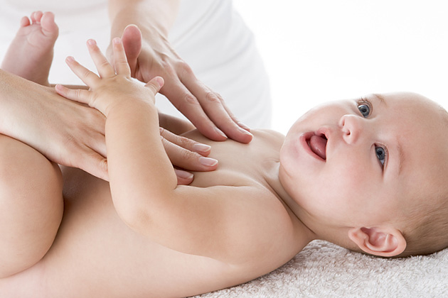 baby massaged by two hands