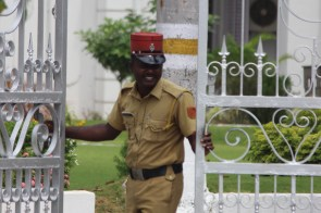 A happy guard closes and impressive gate in front of an even more impressive home. Pondicherry, India.