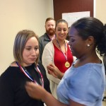 Ieasha presents a medal to Cynthia as an award