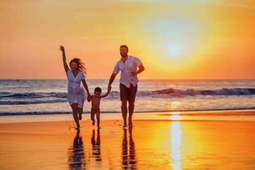happy family running on beach at sunset