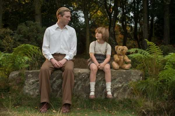 Christopher Robin and dad sitting in forest with teddy bear