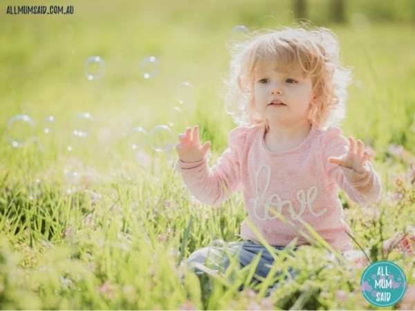 Toddler playing with bubbles outside | Developmental Milestones