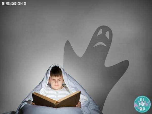 little boy reading scary book with ghost