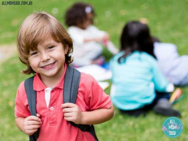 little boy smiling starting school with backpack