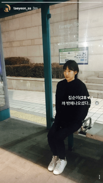 Taeyeon sitting up straight at the bus stop or taxi stand