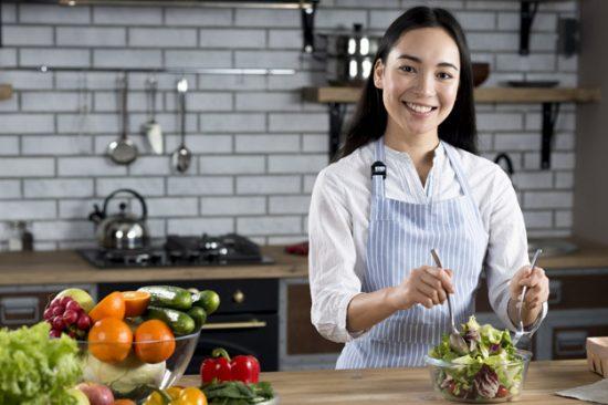 فتاة شابة تقوم بعمل طبق سلطة داخل المطخ