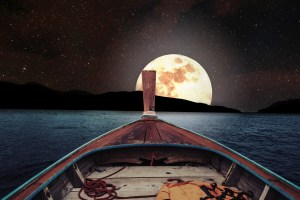 Traveling on wooden boat at night with full moon