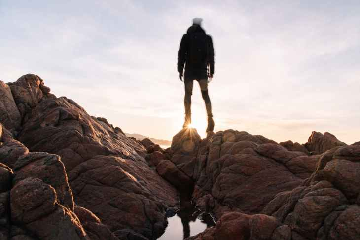 traveler with backpack standing on rocks