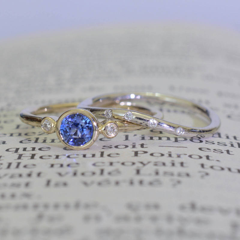 Round blue sapphire bezel with two side diamonds