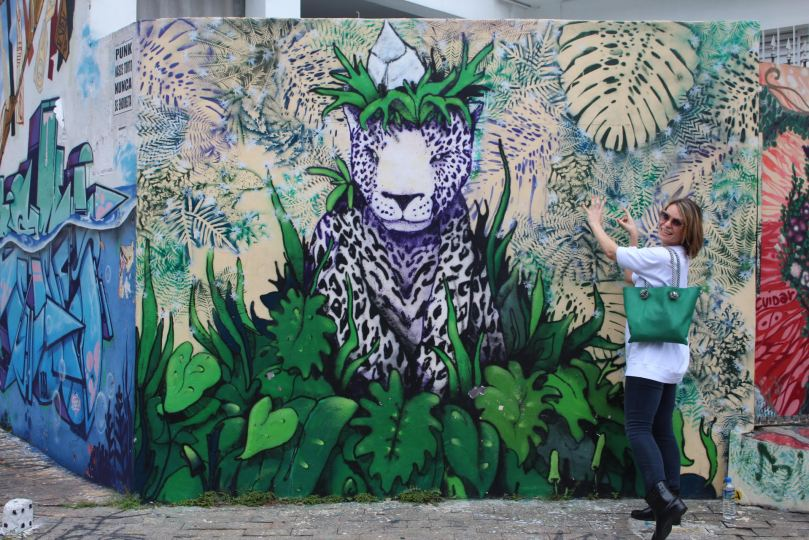 woman showing art mural in São Paulo, Brazil
