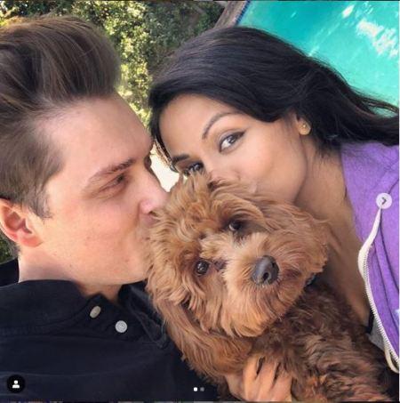 Karen David and her husband kissing their pet dog.