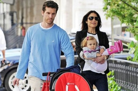 Bethenny Frankel carrying her daughter, Bryn in her arm aside with her husband, Jason Hoppy.