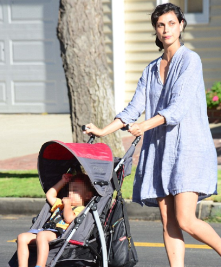 Morena Baccarin currying her child in the street