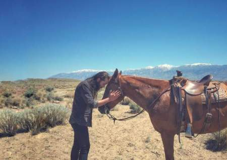 Avi Kaplan is showing his love for a horse in Bishop, California.