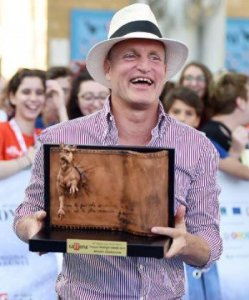 Woody Harrelson holding one of his Award
