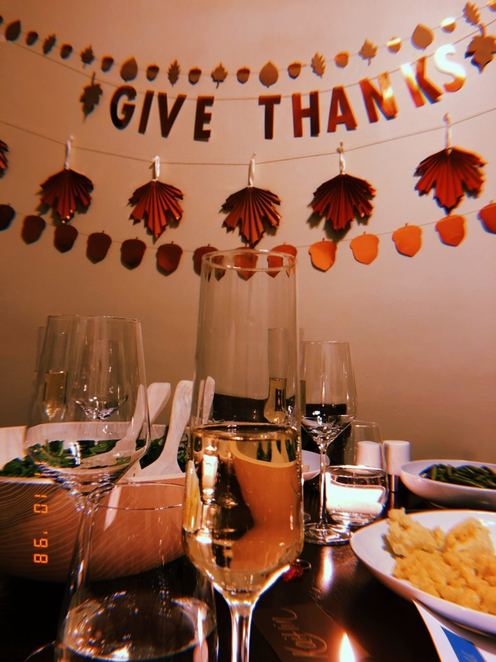 Champagne glass with Friendsgiving dinner in the background