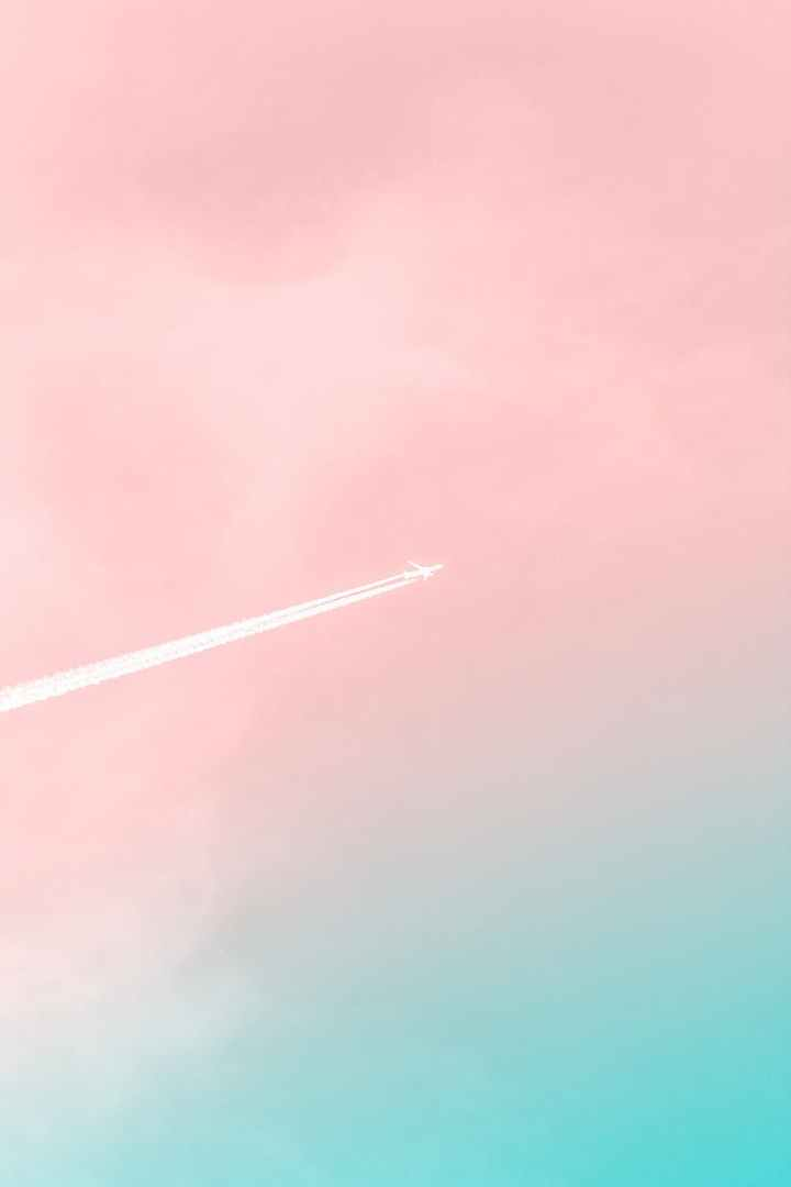 Building the Perfect Welcome Bag for Destination Weddings and Events. Pictured: Plane traveling through pink and blue ombre sky