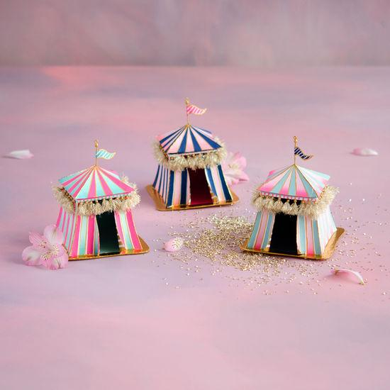 Three small square circus tents in whimsical linear patterns with blue, pink, green and gold color schemes. Glitter and rose petals flood the background.