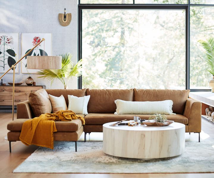 Anthropologie is one of my favorites on this list of Most Loved Sites for Interiors. Pictured: leather l-shaped couch with white pillows and a white wash wooden coffee table