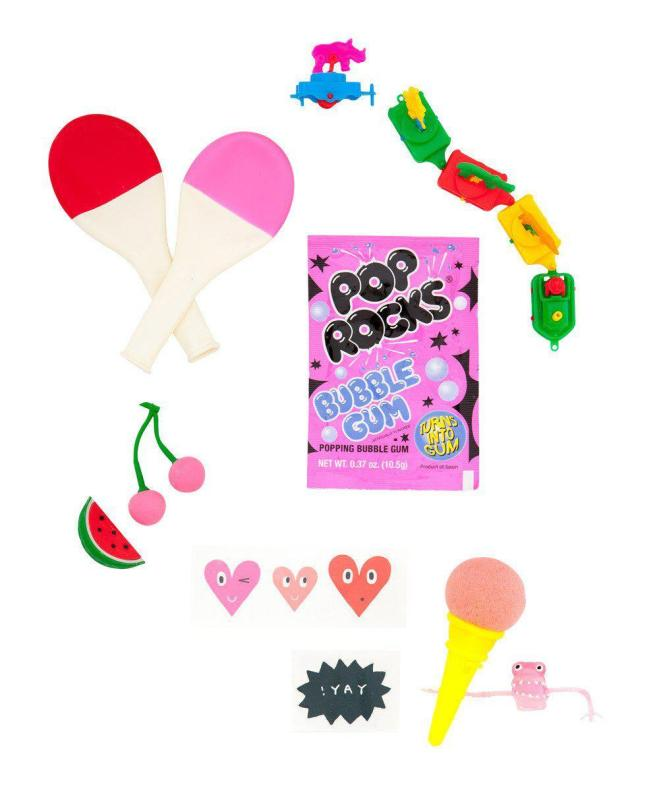 Favor kit materials, including mini ping pong paddles, Pop Rocks candy, stickers, and other goodies
