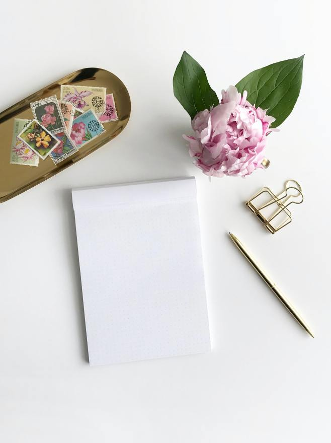 Vintage stamps next to blank piece of paper and gold pen, pink flower and gold paper clip.