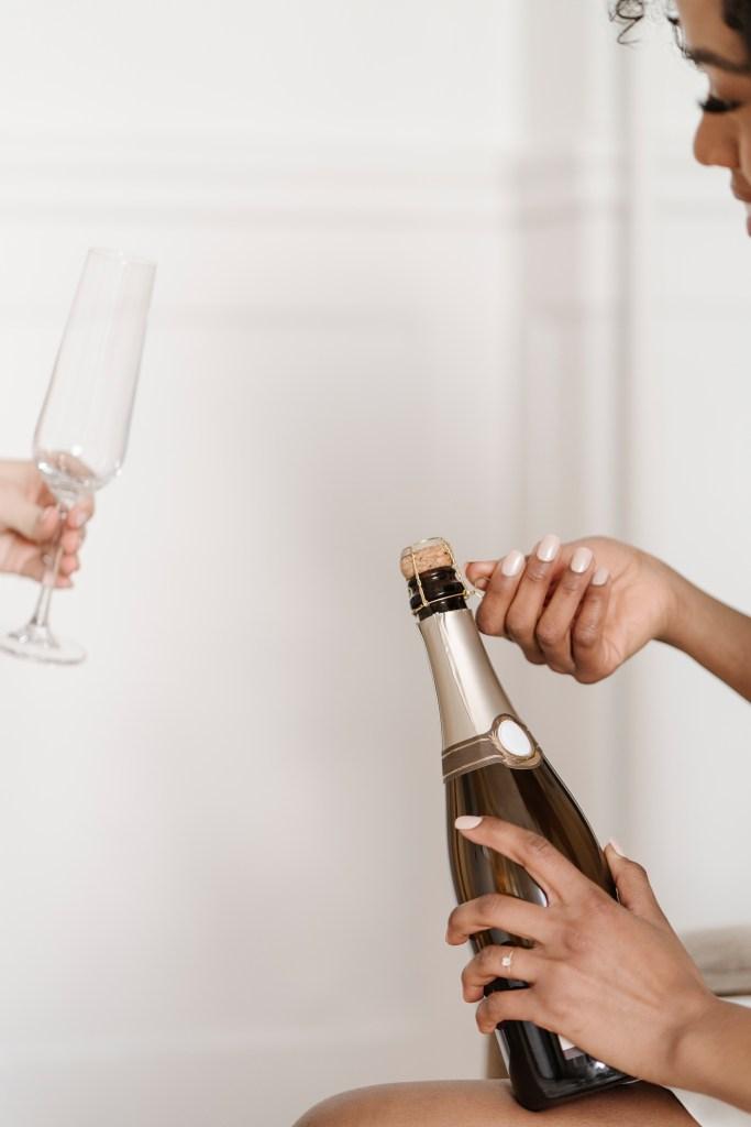 Women popping champagne bottle