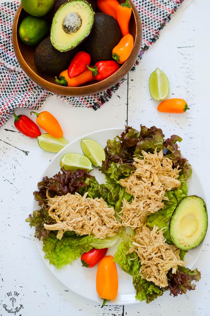 instant pot salsa verde chicken on lettuce tacos on a white plate with a wooden bowl of limes, peppers, and avocado