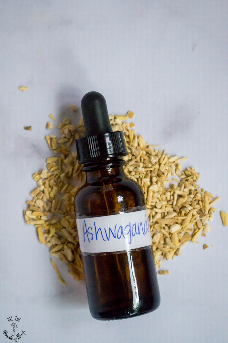 bottle of ashwagandha tincture sitting on dried ashwagandha