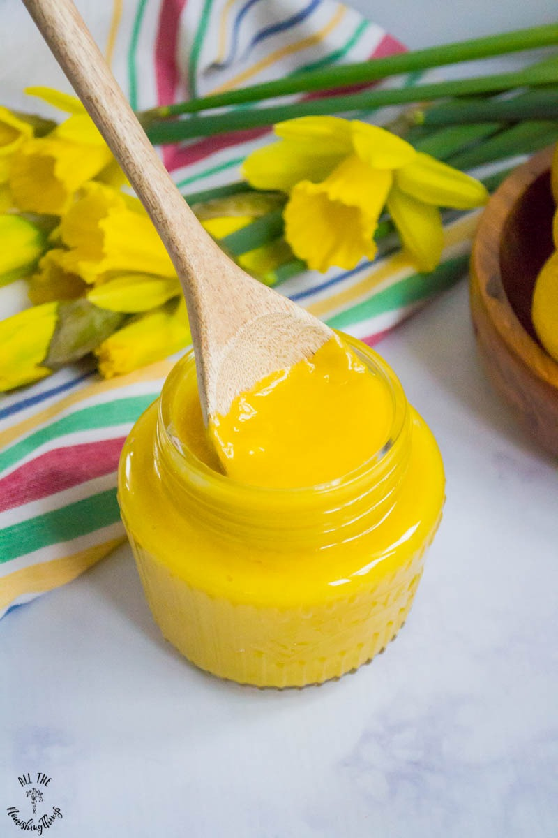 jar of bright yellow keto lemon curd with wooden spoon in the jar