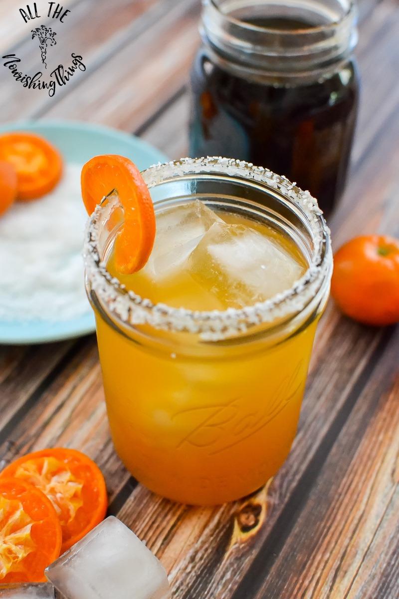 bright orange cocktail in Mason jar garnished with slice of clementine