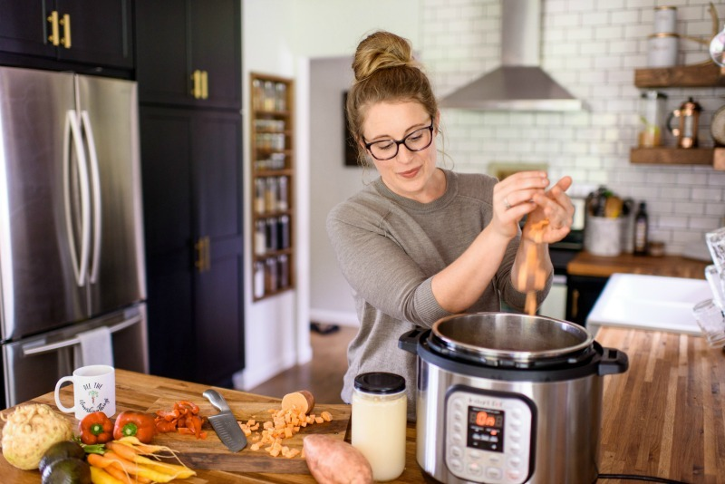woman adding sweet potatoes to her instant pot