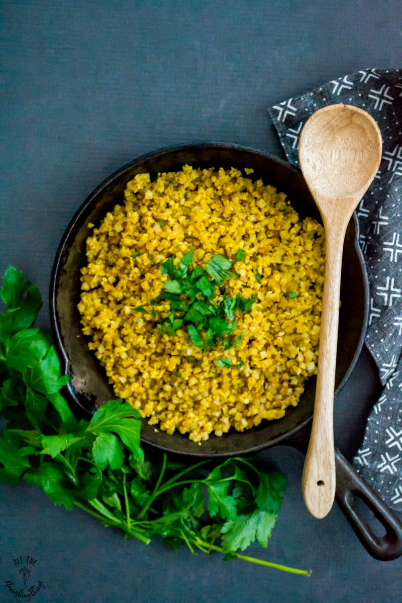 cast iron skillet with yellow turmeric cauliflower rice and wooden spoon