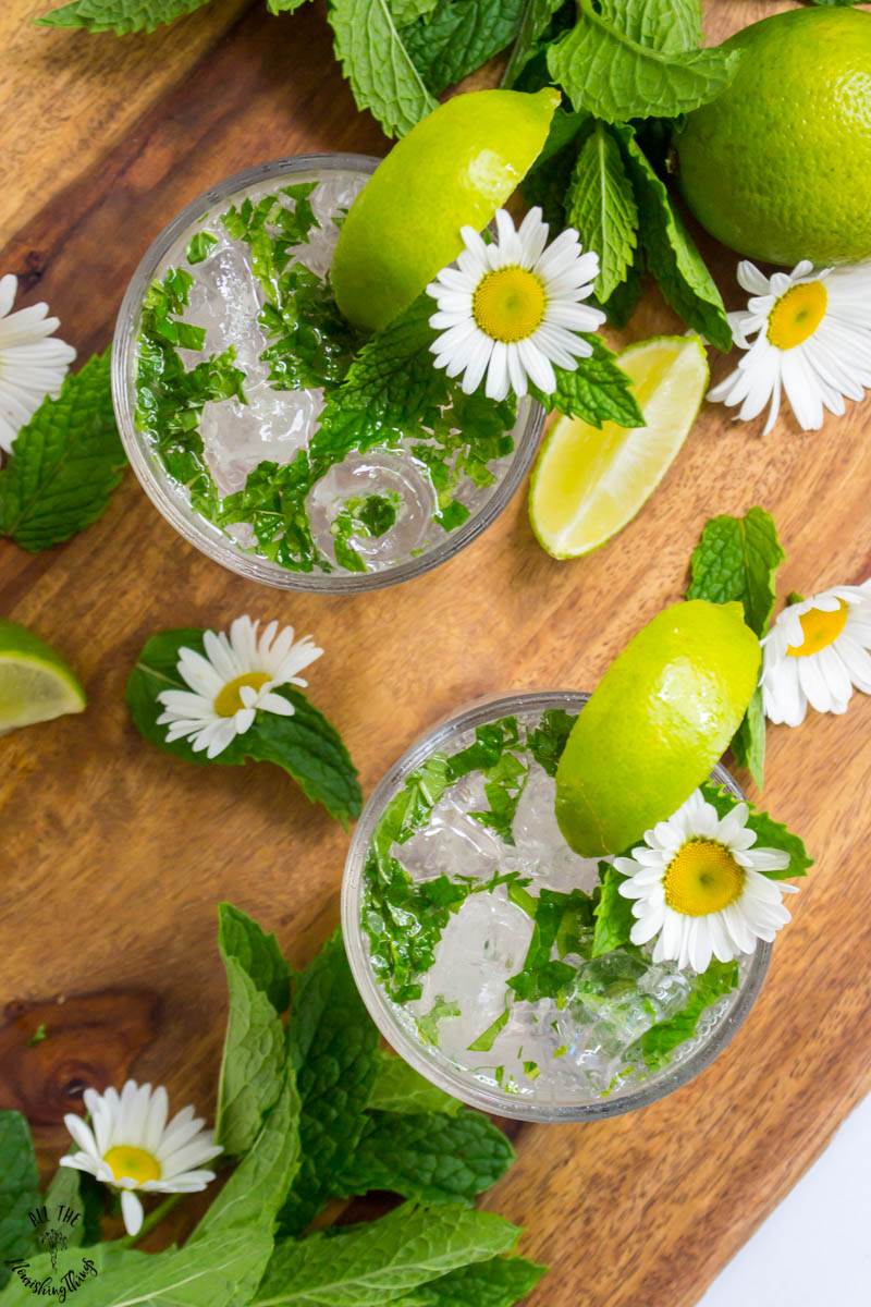 overhead view of keto mojitos garnished with lime wedges, fresh mint leaves, and daisies